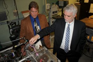 Pictured is President Tim Killeen controlling a glow discharge with a magnet with CPMI Director, Professor David Ruzic